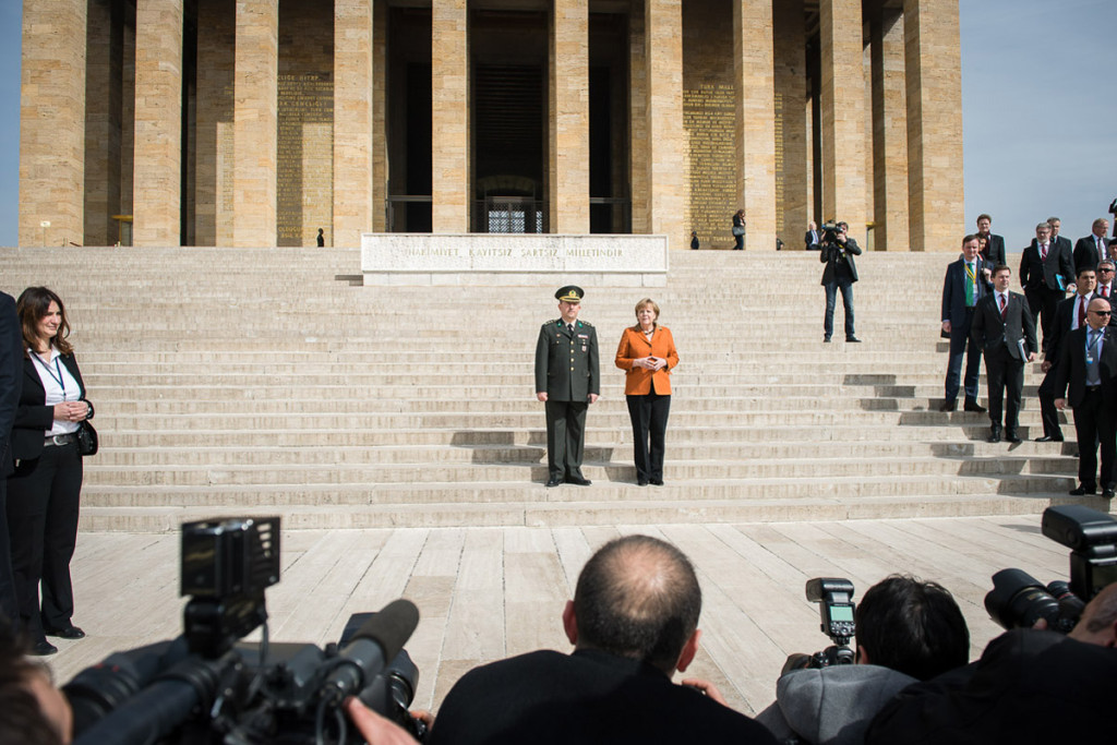 The Chancellor leaves the Atatürk Mausoleum with an officer of the guard of honour.