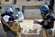 UN inspectors clad in protective clothing take soil samples in Syria