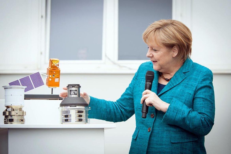 Merkel betrachtet ein Modell eines Satelliten in der Optronik GmbH in Jena.