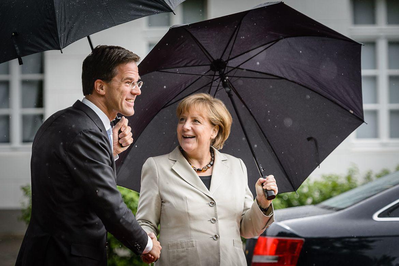 Bundeskanzlerin Angela Merkel reicht Ministerpräsident Rutte die Hand, beide halten Regeschirme in der Hand